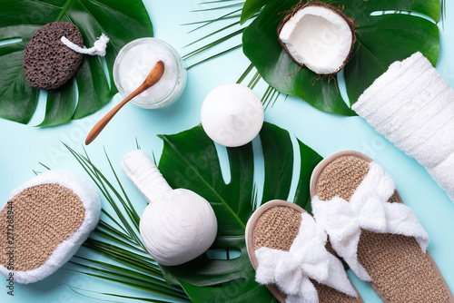 Poster Spa Spa, wwellness, skin care, beauty and relax concept. Spa tools: white towel, bamboo slippers, herbal ball, cream, wooden brush, coconut oil, monstera on blue background.