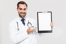 Portrait Of Affable Young Medical Doctor Smiling At Camera And Holding Health Card