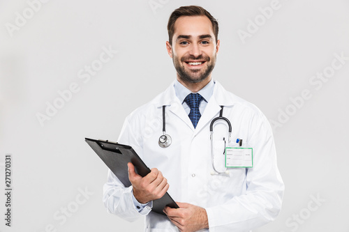 Fotografie, Obraz  Portrait of european young medical doctor smiling at camera and holding health c