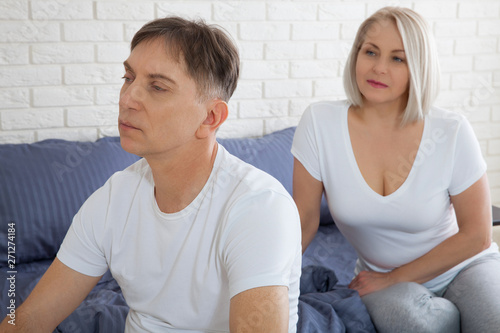 Offended woman and man trying to reconcile in bed Canvas Print