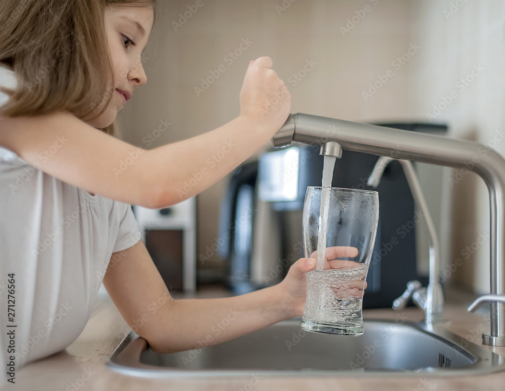 Fototapeta Portrait of a little caucasian girl gaining a glass of tap clean water. Kitchen faucet. Cute curly kid pouring fresh water from filter tap. Indoors. Healthy life concept