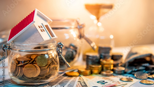 Saving money for retirement concept. Real estate or property investment. Home mortgage loan rate. House model on currency glass jars with coin stack, money bag, banknotes and hourglasses on the table.