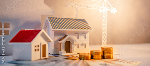 Acrylic Prints Amsterdam Real estate or property development. Construction business investment concept. Home mortgage loan rate. Coin stack on international banknotes with house and construction crane models on the table.