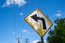 Old, Dilapidated Yellow Curve Ahead Road Sign With Peeling Paint Against Blue Sky With Power Lines