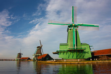 Ancient Green Windmill Located In Zaanse Schans, A Small Dutch Community Along The Quay Of The River Zaan.