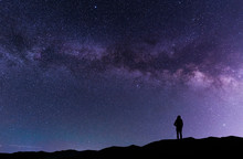 A Silhouette Stands On In The Hill And Looks At The Milky Way Galaxy.