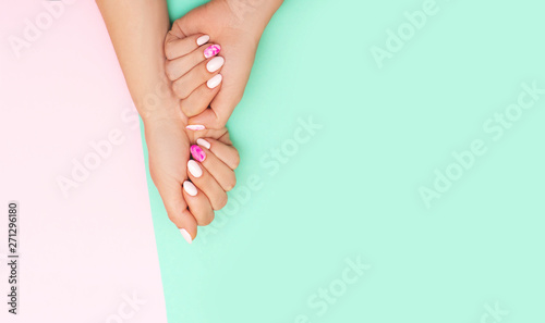 Photographie Top view of perfect manicure with trendy nail art on pink and turqoise backgroun