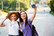 Selfie time. Two female friends taking self pictures during the journey at city park background