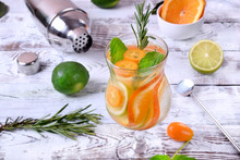 Sparkling Beverage With Slices Of Lime, Kumquat And Orange Topped With Mint Against The White Wooden Background