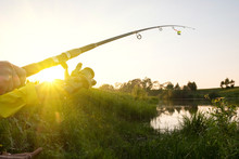 Fishing Rod On The Lake Bent Under The Weight Of Fish At Sunset. Fishing Rod Sunset Rays