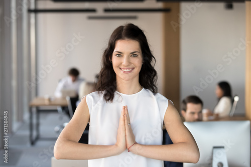 Fotografía Portrait of smiling female employee meditate in prayer pose