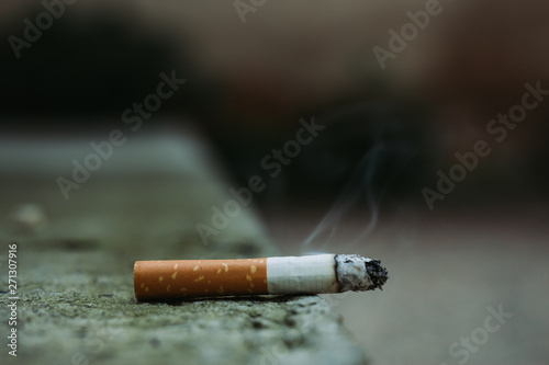 Fotografia, Obraz  Lit white cigarette with orange filter and smoke coming out of it sitting on the