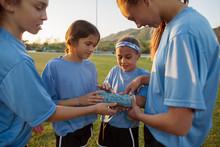 Girls Looking At Plaster Cast Of Friend's Broken Arm In Grassy Field