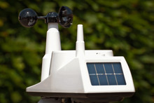A Device That Measures Speed, Force And Direction Of The Wind. White Anemometer With Solar Panels On A Green Background.