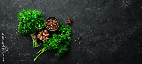 Parsley, spices and herbs. On a black stone background. Top view. Free space for your text.