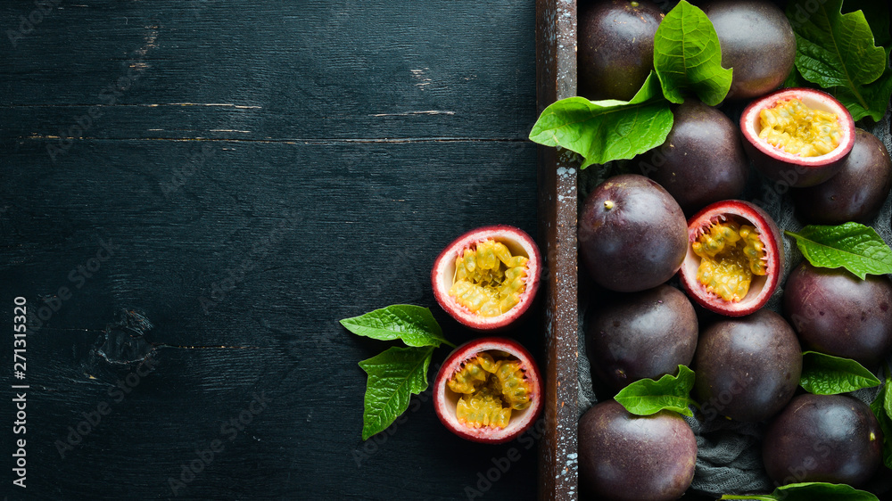 Fototapeta Fresh passion fruit with leaves in Wooden Box. Tropical Fruits. Top view. Free space for text.
