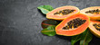 canvas print picture - Fresh papaya on a black stone background. Tropical Fruits. Top view. Free space for text.