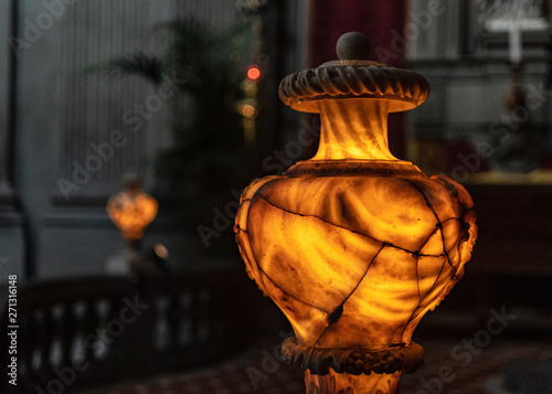 ancient illuminated alabaster vase shows the face of Medusa and numerous cracks Wallpaper Mural