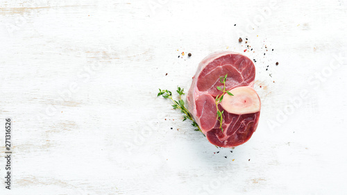 Stampa su Tela Raw fresh cross cut veal shank with spices and herbs on a white background