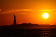 statue of liberty at sunset with silhouette and sun and orange sky