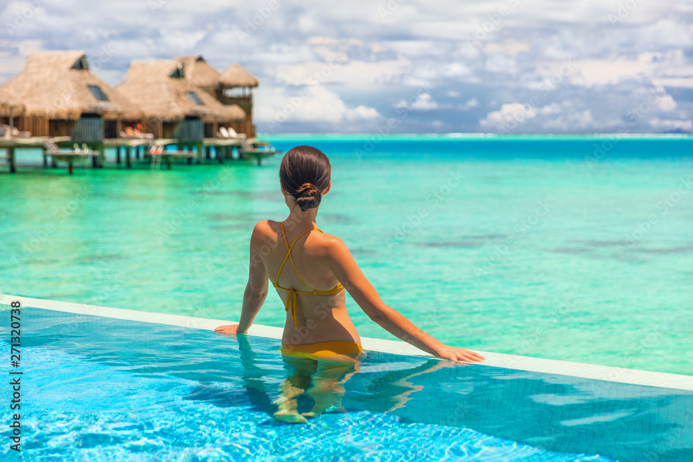 Fototapeta Luxury overwater bungalow hotel room with infinity swimming pool woman looking at blue ocean view. Tropical travel summer vacation lifestyle.
