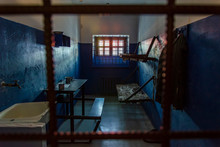 Empty Prison Cell In The Worst Prison In Russia. Two Beds, A Table, A Washstand And A Toilet Are Behind Bars.