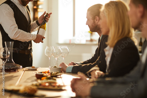 Fotografía  Mid section portrait of professional sommelier presenting wine to group of peopl