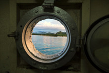 Indonesia, View At Lombok Coastline In Porthole Of Ferry