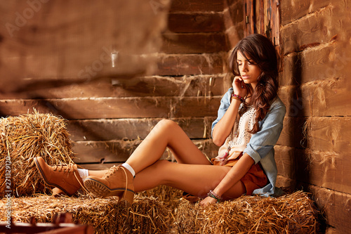 Canvas Print brunette in the image of a cowboy in a denim shirt, short shorts and boots, sits