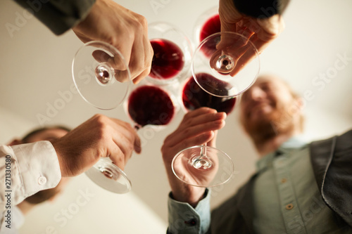 Fotografie, Obraz Low angle view at group of people in formalwear clinking wine glasses during eve