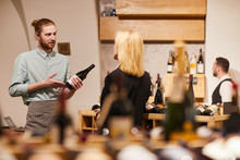 Portrait Of Contemporary Man Consulting Customer In Liquor Store, Copy Space