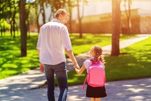 Father Leads Daughter To School In First Grade. First Day At School. Back To School.