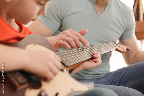 Canvastavla Little boy playing guitar with his teacher at music lesson, closeup