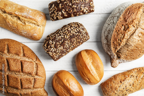 Foto op Aluminium Brood Different kinds of fresh bread on wooden table, flat lay.