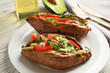 Plate with stuffed sweet potatoes on white wooden table, closeup