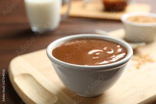 Foto op Plexiglas Chocolade Bowl with caramel sauce on board, closeup