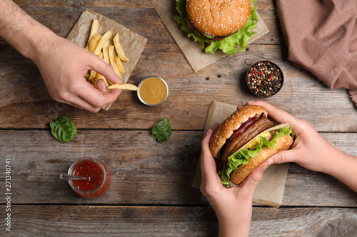 Fotografia, Obraz  People with burger and French fries at wooden table, top view