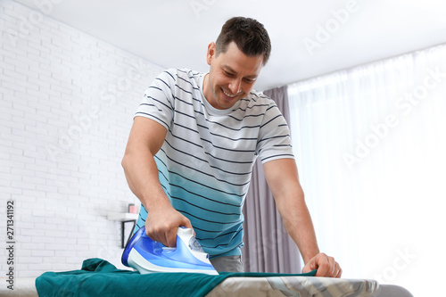 Fotomural Man ironing clothes on board at home