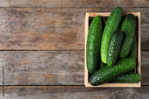 Photo  Crate full of fresh ripe cucumbers on wooden background, top view