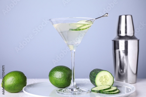 Photo Composition with glass of cucumber martini on table against color background, sp