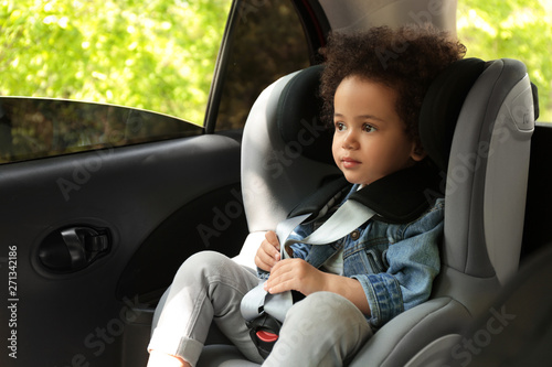 Fényképezés Cute African-American child sitting in safety seat inside car