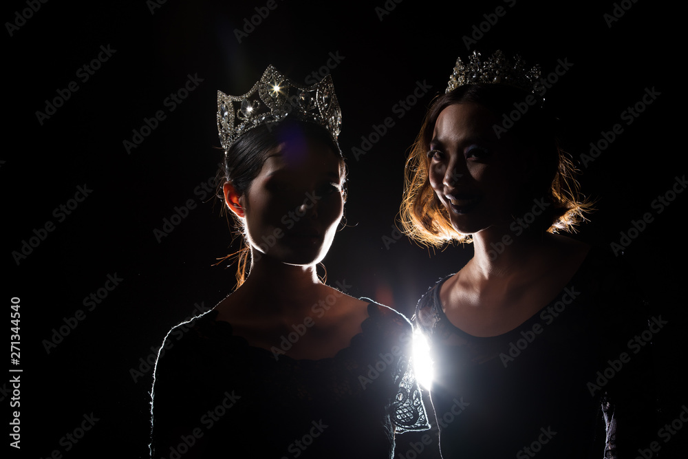 Fototapety, obrazy: Two Silhouette Shadow Back Rim Light of Miss Pageant Beauty Queen Contest with Silver Diamond Crown stand together, studio lighting dark black background, multinational asian and caucasian models