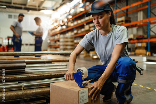 Fotografía  Female worker using tape dispenser gun while packing boxes for the shipment
