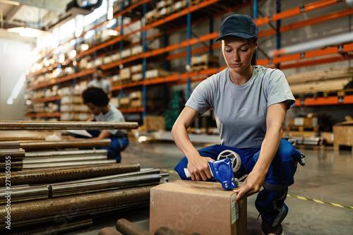 Obraz Female warehouse worker packing cardboard boxes for the shipment. - fototapety do salonu
