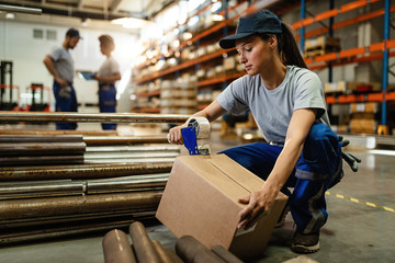 Young woman working in warehouse and taping cardboard box for shipment.