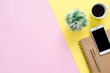 canvas print picture Office desk working space - Flat lay top view of a working space with white blank notebook page, coffee cup and mock up phone on pastel background. Pastel pink yellow color background space concept.