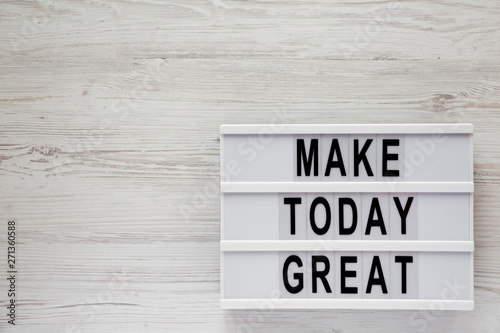Photo  'Make today great' words on a light box over white wooden background, top view