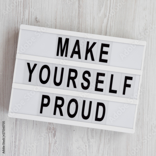 Fényképezés Light box with text 'Make yourself proud' on a white wooden background, top view