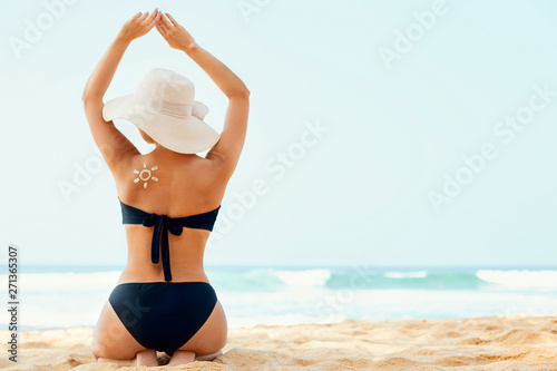 Photo  Beautiful woman in bikini applying sun cream on tanned shoulder