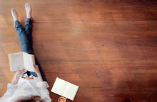 Top View Of Young Woman Holding Book With Blank Page While Sitting On Wooden Floor, Copy Space.